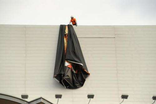 "Workers remove a poster-banner for ""The Interview"" from a billboard in Hollywood, California on December 18, 2014 a da"