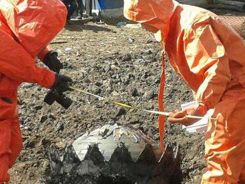 Photo taken on May 19, 2014  shows government technicians preparing to remove space debris that crashed to the ground in Qiqihar