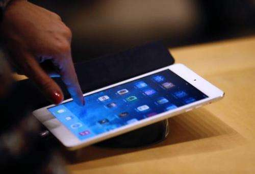 A woman looks at an Apple iPad at one of the company's stores in Paris, on December 20, 2013