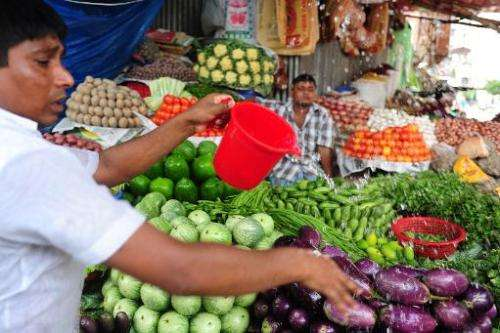 A Bangladeshi vendor washes vegetables in Dhaka on August 10, 2012