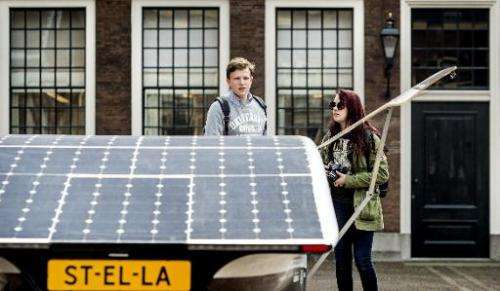 """A boy and a girl stand next to the Dutch solar-powered car """"Stella"""" in front of the Binnenhof, the Dutch Parliament bu"""