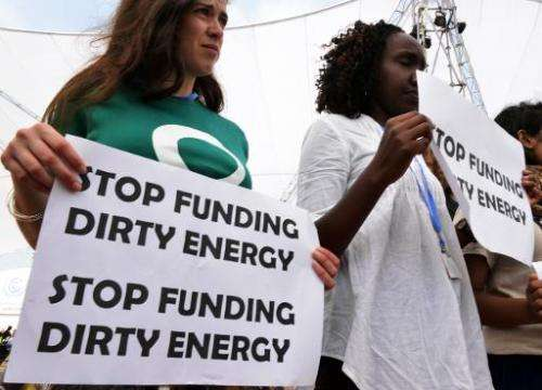 Activists hold banners challenging public money going to financing dirty energy in the COP20 grounds in Lima on December 3, 2014