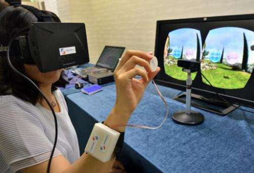 """A journalist tries to use """"3D-Haptics Technology"""", at a press preview in Tsukuba, suburban Tokyo on September 1, 2014"""
