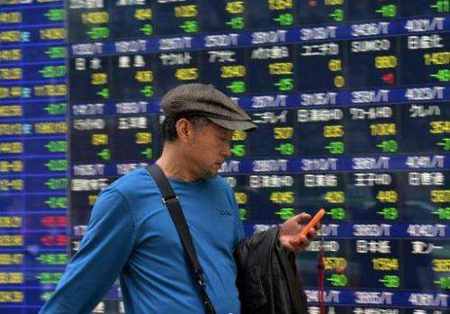 A man checking his smartphone as he walks past an electronic share prices board in Tokyo