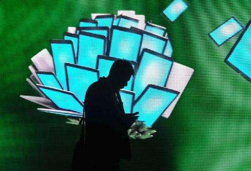 A man checks a mobile device during the 2014 Mobile World Congress in Barcelona on February 26, 2014