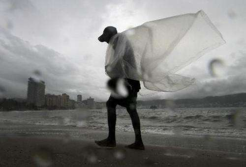 A man walks by a beach during the passage of a storm in Acapulco, Mexico on September 17, 2014