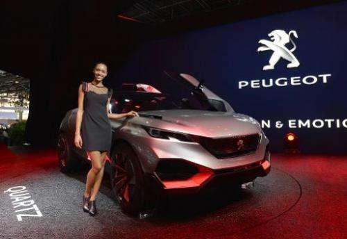 A model poses next to the new Peugeot Concept Car Quartz at the Paris Auto Show in Paris on October 2, 2014