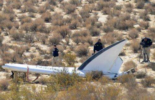 A National Transportation Safety Board (NTSB) team surveys a tail section from the crashed Virgin Galactic SpaceShipTwo near Can
