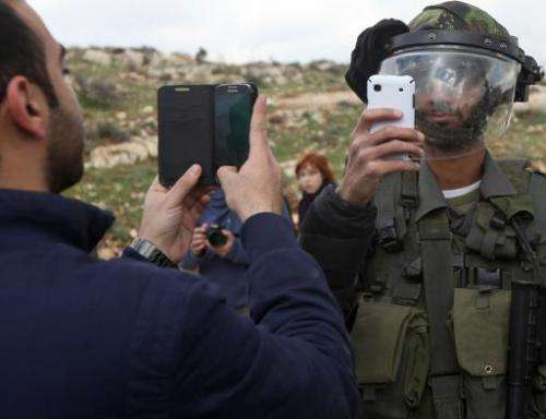 A Palestinian man and a member of the Israeli security forces take pictures of each other with their mobile phones in Nabi Saleh