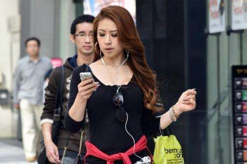 A pedestrian using her smartphone on a street in Tokyo, November 3, 2014. Growing ranks of cellphone addicts are turning cities
