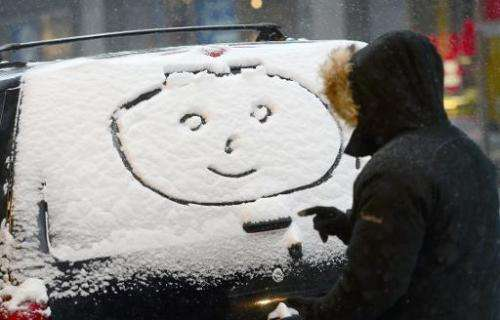 """A person draws a """"happy face"""" on a car window during a snow storm in New York, January 21, 2014"""