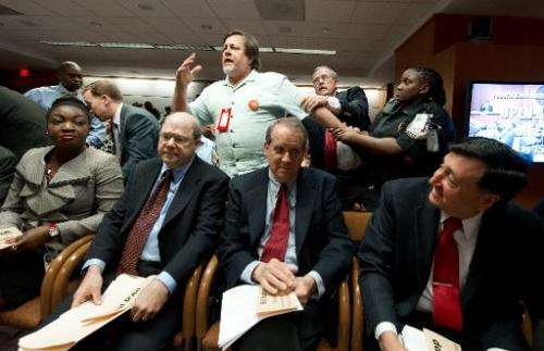 A protester is pulled from meetings of the Federal Communications Commission (FCC) commissioners on May 15, 2014 at the FCC in W