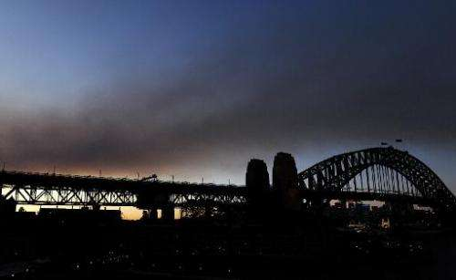 A smoke haze creates an unusual sunset over the Sydney Harbour Bridge following hazard reduction burning in the Blue Mountains,
