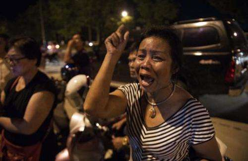 A Thai pro-government supporter cries and shouts insults at Thai army soldiers as they stand guard at the main entrance of the p