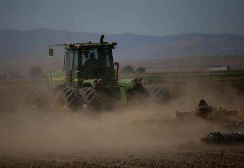 A tractor kicks up dust in an unplanted field on September 5, 2014 in Los Banos, California as California suffers its third year