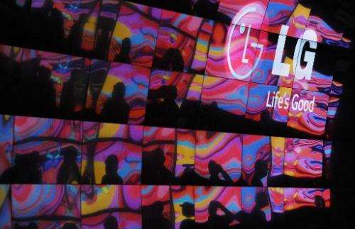 Attendees and images from other 4K TVs are reflected in the curved 4K 3D Cinema display at LG's booth at the 2014 International