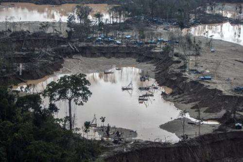 """A view of camps surrounding pumps used for illegal gold mining in Mega 13, in Peru's """"Mother of God"""" region"""
