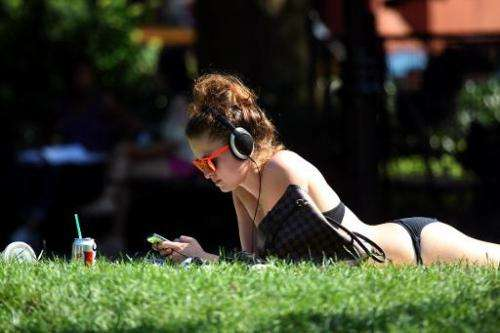 A woman suns herself on Washington Square Park in New York City on July 16, 2013 as a heatwave descended on the city