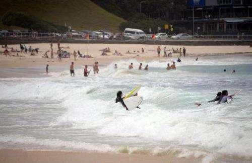 Beachgoers enjoy the waves at Bondi Beach in Sydney on October 28, 2014