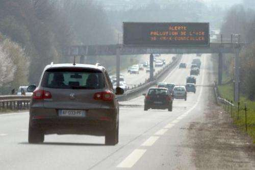 """Cars drive past a traffic board reading """"Warning air pollution 90 km /h recommended"""" near Rennes, western France on Ma"""