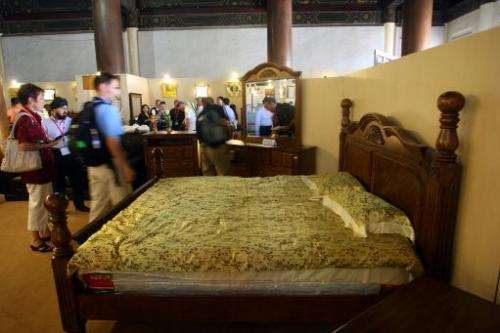 Chinese customers admire a luxury bed at a furniture fair in Beijing on June 23, 2010