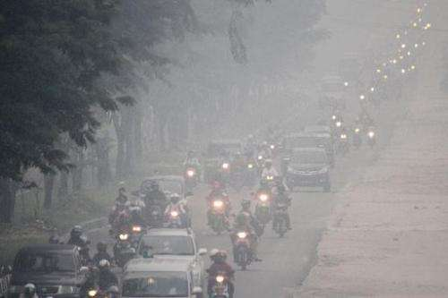 Commuters travel along a road as thick haze blankets Pekanbaru in Indonesia on September 16, 2014