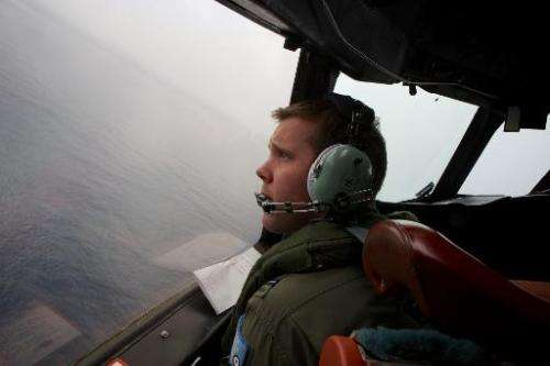 Co-Pilot, Flying Officer Marc Smith turns his RAAF AP-3C Orion aircraft whilst searching for flight MH370 over the Indian Ocean