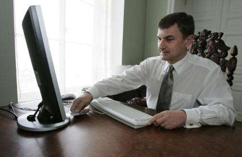Estonian Prime Minister Andrus Ansip inserts a card to validate his electronic ballot through the web on February 26, 2007 from