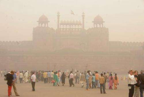 In this photograph taken on November 7, 2009, pedestrians and visitors gather as smog envelopes The Red Fort in New Delhi