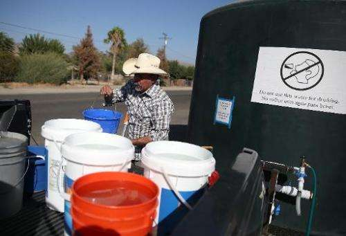 Mario Garcia fills buckets with non-potable water from a tank set up in front of the Doyle Colony Fire Station in Porterville, C