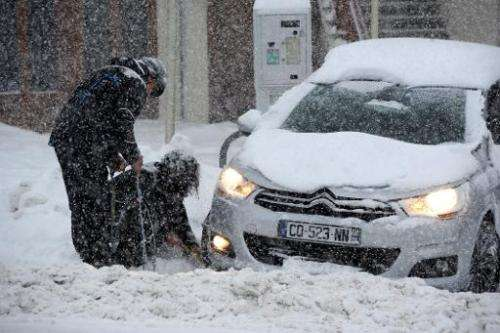 People put snow chains on their tires as snow falls on December 27, 2014 on the road to the Les Saisies ski resort in Savoie, ce