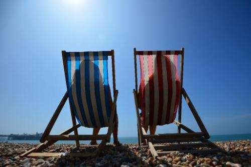 People relax on the beach in Brighton, England, on July 18, 2014, as the Met Office issued a heatwave alert for southern England