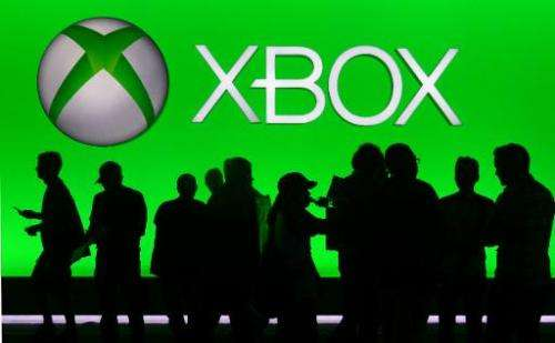 People silhouetted against an Xbox display at annual E3 video game extravaganza in Los Angeles, California on June 10, 2014