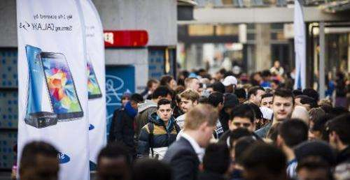 People stand in line outside a store during the launch of the Samsung Galaxy S5 in Rotterdam on April 11, 2014