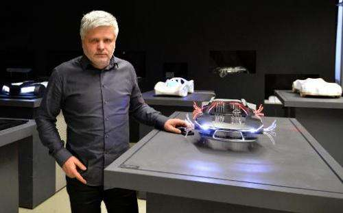 Photo taken on December 17, 2013 shows Slovak engineer Stefan Klein posing with his car models in Bratislava, Slovakia