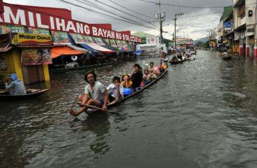 Residents ride on wooden boats in the town of Santa Cruz, south of Manila, on October 4, 2009, one week after tropical storm Ket
