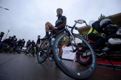 Riders wait for the start of the second stage of the 2014 Tour of Beijing in Chongli town, near Zhangjiakou, in China's Hebei Pr