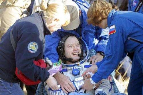 Russian doctors help US NASA astronaut Steven Swanson (C) after he returned with two Russian cosmonauts from the International S