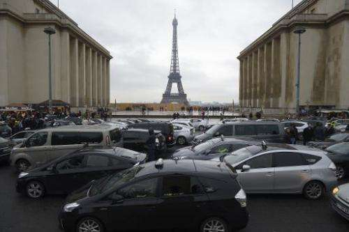 "Taxi drivers take part in a ""snail operation"" after parking their cars on the Trocadero square in Paris, on December 1"
