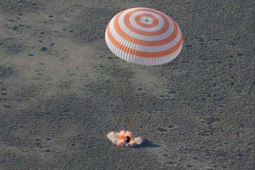 The Russian Soyuz TMA-011M space capsule lands about 150 km (90 miles) south-east of the Kazakh town of Dzhezkazgan, in Kazakhst