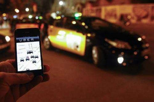 The Uber app is seen on a smartphone as cabs wait for clients near the Sagrada Familia in Barcelona, on December 9, 2014