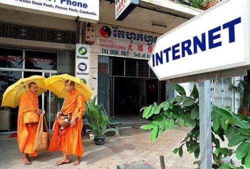 Two Cambodian Buddhist monks stand outside an early Internet cafe in Phnom Penh, in December, 2000