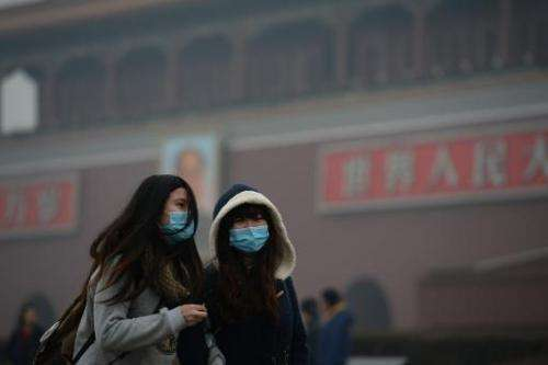Two girls walk through a haze-shrouded Tiananmen Square in Beijing on February 23, 2014