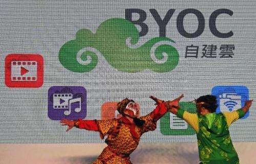 Two performers demonstrate in front of a logo of Acer's latest technology Build Your Own Cloud during a press conference in Taoy