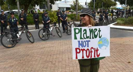 A climate protester holds up a placard in Cairns on September 21, 2014