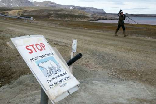 A scientist walking past a warning sign reading 'stop, polar bear danger, do not walk beyond this sign without your firearm', at
