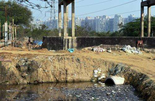 Construction can be seen near a drainage canal carrying refuse water from residential apartment buildings in the Dwarka sector o