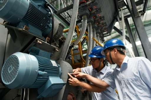 Engineers checking a machine they designed in a factory in Zouping, eastern China's Shandong province on June 30, 2015