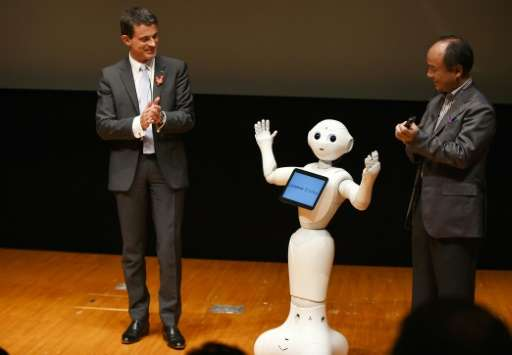 French Prime Minister Manuel Valls (L) meets Softbank's humanoid robot 'Pepper', at the National Museum of Emerging Science and