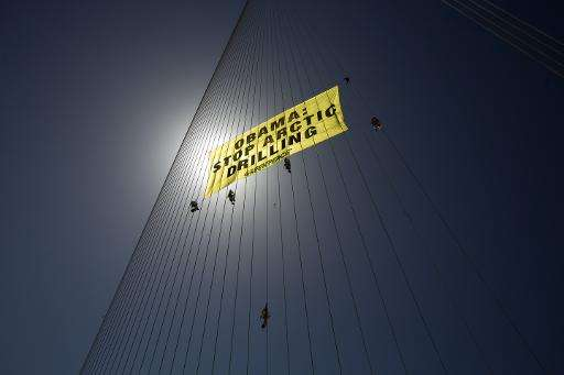 Green Peace activists climb on the strings of Jerusalem''s Chords Bridge during a protest on March 21, 2013, hanging a banner sa